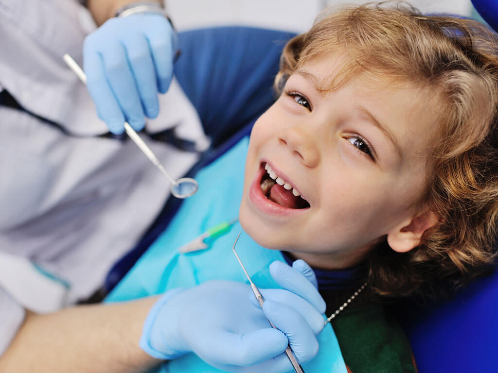 Child Smiling in Dentist Chair