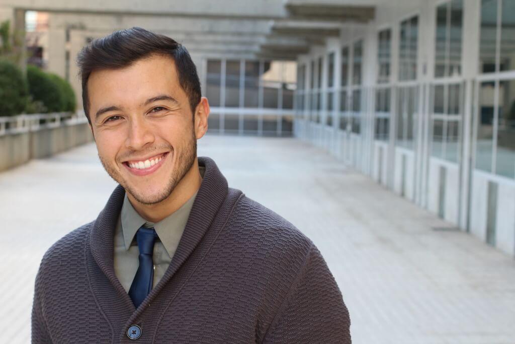Man in cardigan smiling